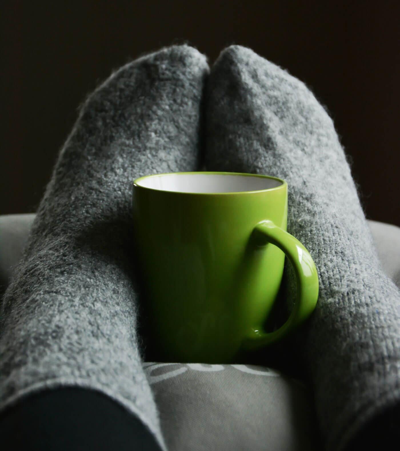 En kop varm te mellem fødder med uldsokker